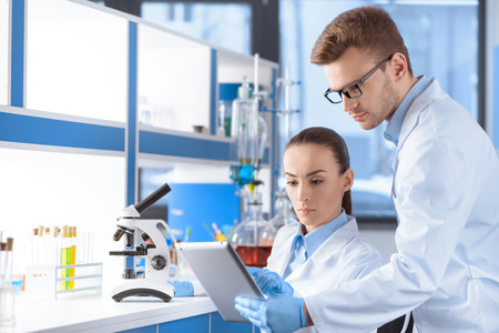 scientists using digital tablet for analysis in laboratory