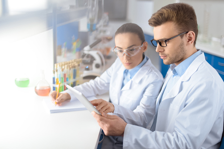 concentrated scientists using digital tablet during work in laboratory Stock Photo