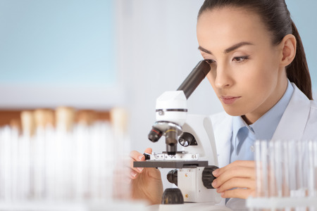 woman scientist working with microscope in laboratory