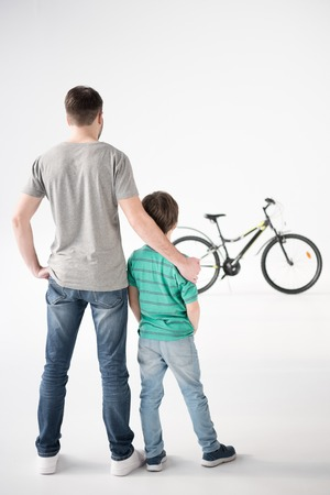 father and son looking at bicycle on white Stock Photo