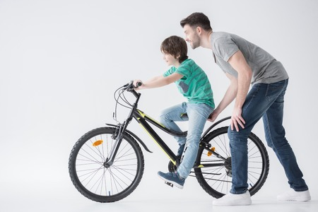 boyhood: father helping son to ride bicycle on white