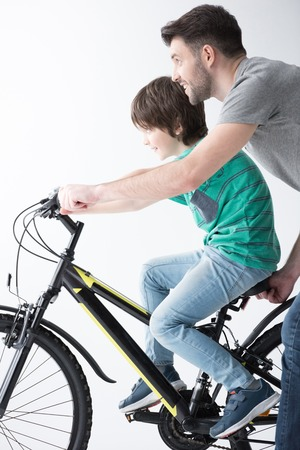 smiling father holding bicycle with son on it on wh Stock Photo