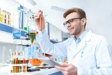 scientist holding digital tablet and looking at test tube in lab