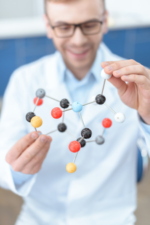scientist in lab coat holding molecular model 免版税图像