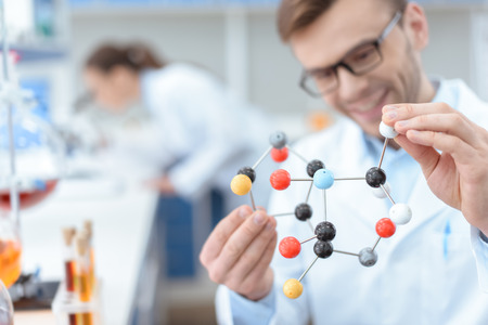 scientist in eyeglasses holding molecular model in lab Stock Photo