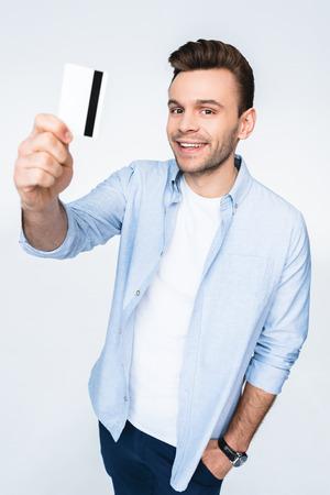 man holding credit card and smiling at camera