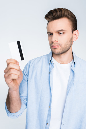 man holding credit card in hand on white