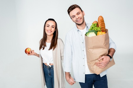 couple holding hands while standing with grocery bag and apple Stock Photo