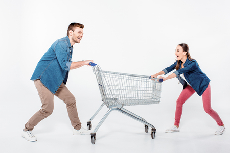 empty shopping cart: couple pulling empty shopping cart and looking on each other on white Stock Photo