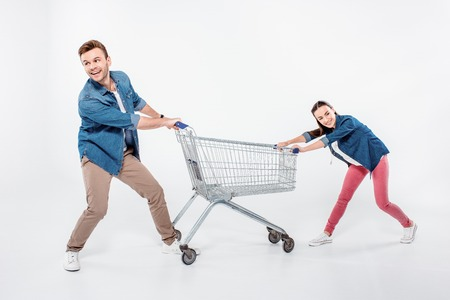 couple pulling empty shopping cart and looking away on white