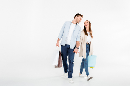 couple walking with shopping bags and looking at each other