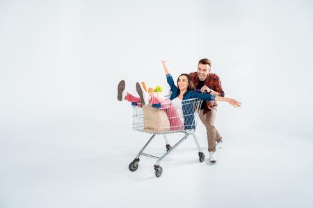 man duwen winkelwagentje met opgewonden vrouw en boodschappen tas op wit