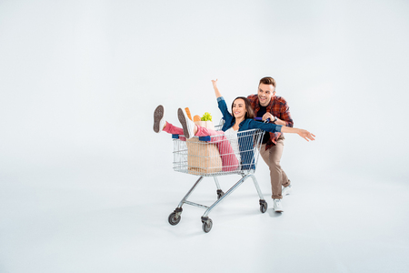man pushing shopping cart with excited woman and grocery bag on white Stock Photo