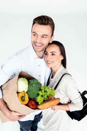 couple with grocery bag smiling and looking away