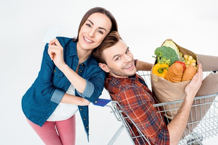 man sitting in shopping cart with grocery bag and woman showing blank card