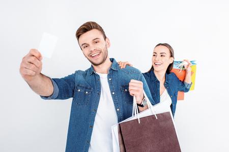 lachende paar bedrijf boodschappentassen en creditcard op wit Stockfoto