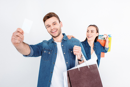 smiling couple holding shopping bags and credit card on white Banco de Imagens