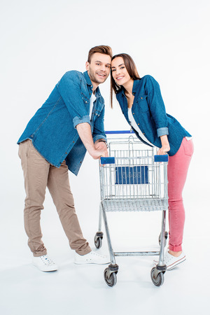 empty shopping cart: couple with empty shopping cart smiling at camera