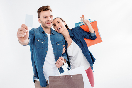 couple holding shopping bags and credit card on white