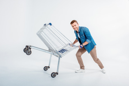 man having fun with shopping trolley on white