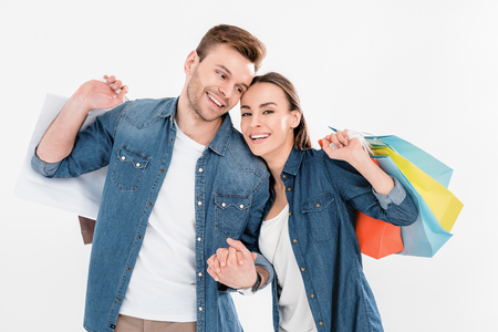 smiling couple holding shopping bags on white, woman looking to camera