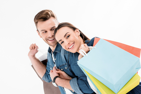 smiling man looking at woman with shopping bags on white Stock Photo