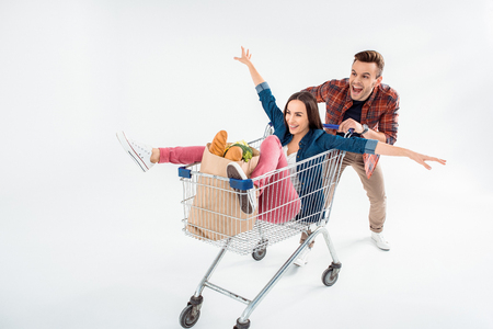 man pushing shopping cart with excited young woman and grocery bag