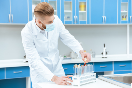 man scientist in protective mask working with test tubes in laboratory