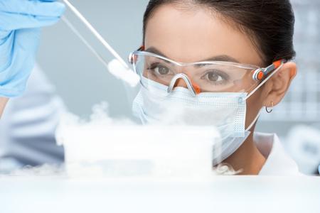Frau Wissenschaftler in Schutzbrille und Maske machen Experiment im Labor Standard-Bild - 72658266