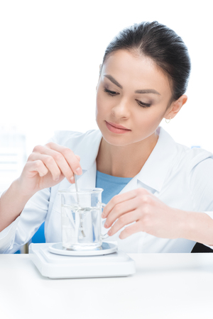 concentrated scientist working with chemical liquid in lab on white Stock Photo