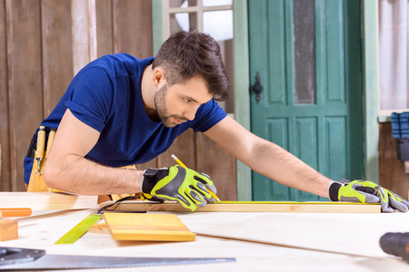 concentrated carpenter in protective gloves taking measures of wooden plank Stock Photo