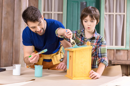 father and son with paintbrushes painting wooden birdhouse together Stock Photo