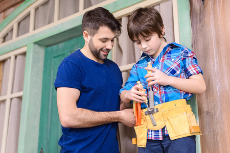 tool belt: father looking at son standing in tool belt and holding tools