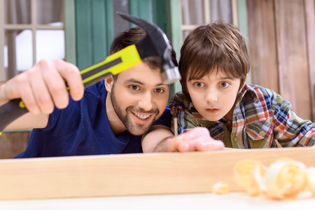 father and son hammering nail in wooden plank Stock Photo