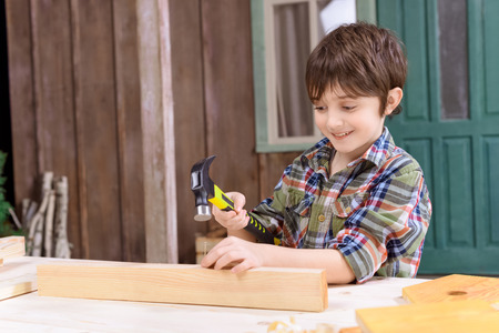 boy in checkered shirt hammering nail in wooden plank