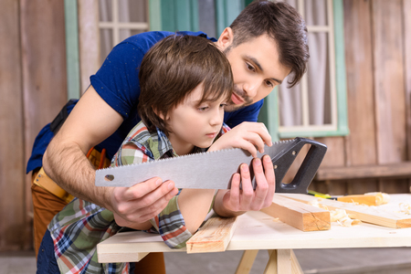 father and son leaning on wooden table and inspecting hand saw