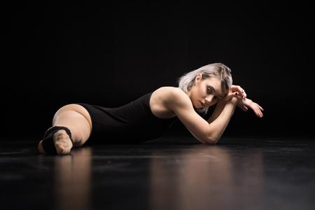 Athletische Frau Tänzerin auf schwarzem Stretching Standard-Bild - 72278525