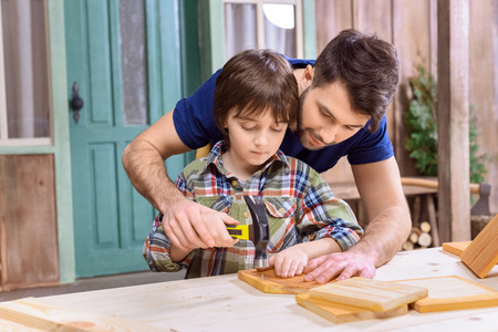 father teaching concentrated son to hammering nail in wooden plank Stock Photo
