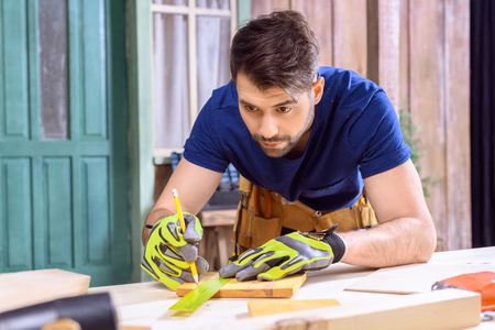 concentrated carpenter taking measures of wooden plank
