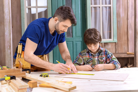 father showing son how to take measures of wooden plank