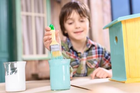 boy holding paintbrush while painting handmade birdhouse