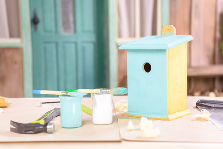 handmade small birdhouse with paints and tools on table 版權商用圖片