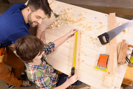happy father looking at son measuring wooden plank with measure tape 写真素材