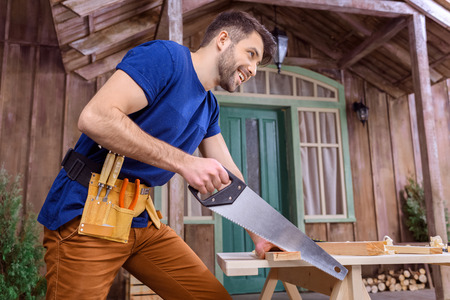 tool belt: smiling bearded carpenter in tool belt sawing wooden plank on porch