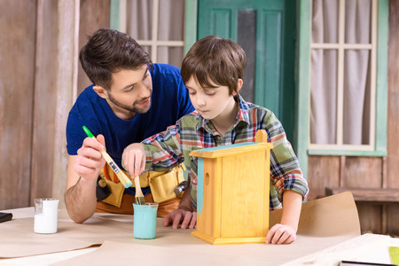 nesting: father and son painting wooden birdhouse together Stock Photo