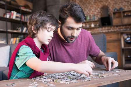 father and son playing with puzzles at home