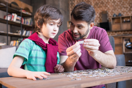 father showing son how to playing with puzzles