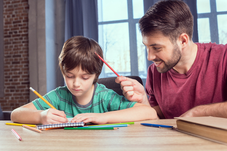 Padre aiutando il figlio concentrato a fare i compiti