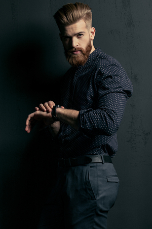 handsome bearded man hipster with wristwatch looking at camera