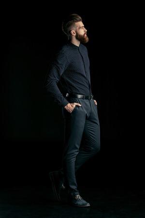 stijlvolle knappe bebaarde man poseren met handen in de zakken op zwart Stockfoto
